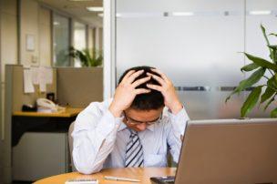 解雇で頭を抱える人